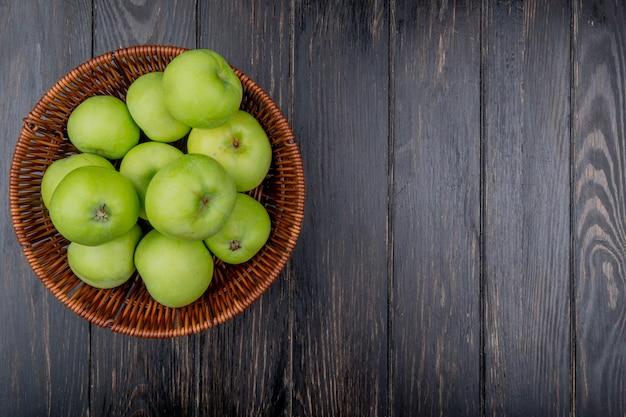 Vista superiore della merce nel carrello verde delle mele su fondo di legno con lo spazio della copia