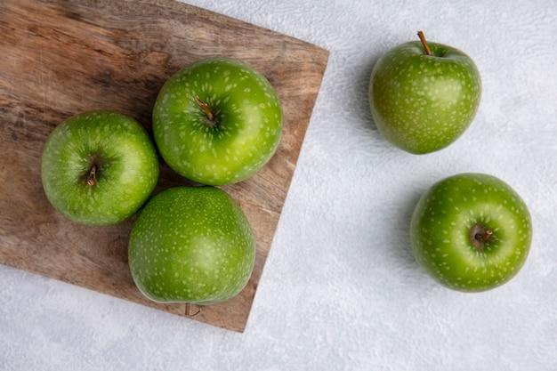 Vista dall'alto mele verdi su una tavola su uno sfondo bianco