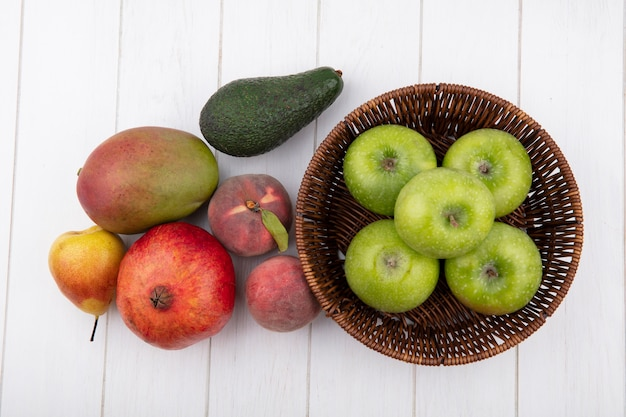 Top view of green apples on a bucket with pomegranate mango pear peach isolated on white surface