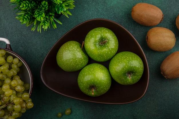 Вид сверху зеленые яблоки в миске с киви и зеленым виноградом на зеленом фоне