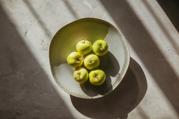 Взгляд сверху зеленые яблоки в плите на текстурированной таблице. горизонтальный