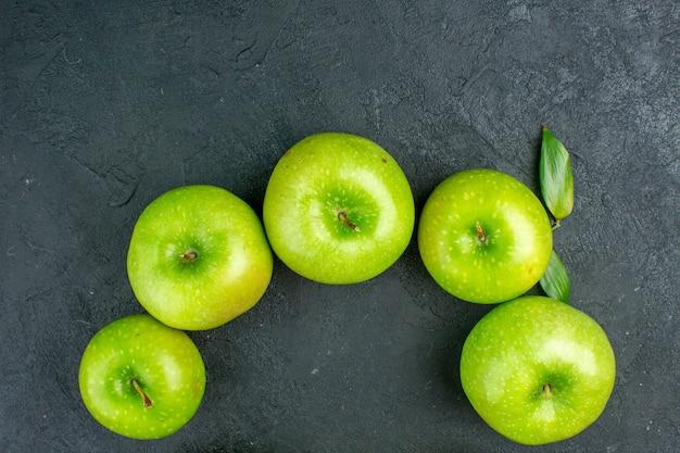 Вид сверху зеленые яблоки на темной поверхности копией пространства