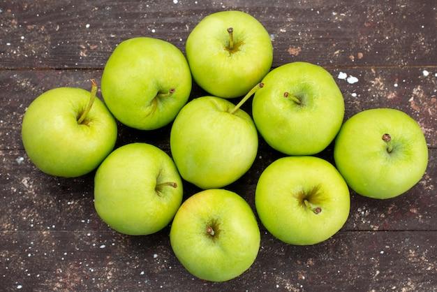 Вид сверху зеленые яблоки на коричневом деревянном столе свежее яблоко фрукты спелые