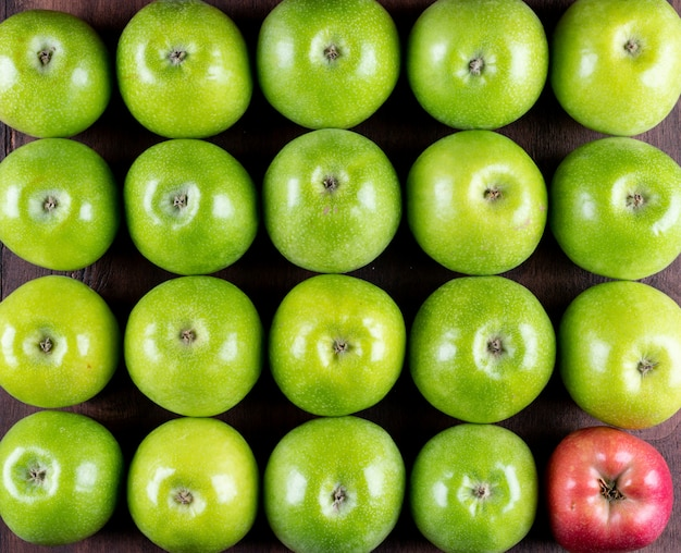 Top view green apples and one red in corner pattern on black wooden  horizontal