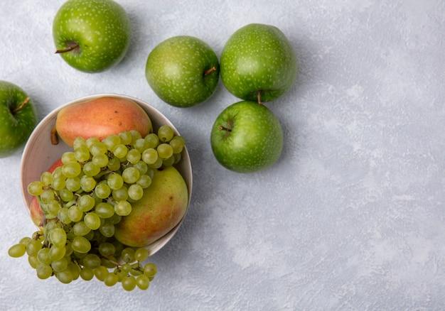 Vista dall'alto mele verdi con uva verde e pere in una ciotola su uno sfondo bianco