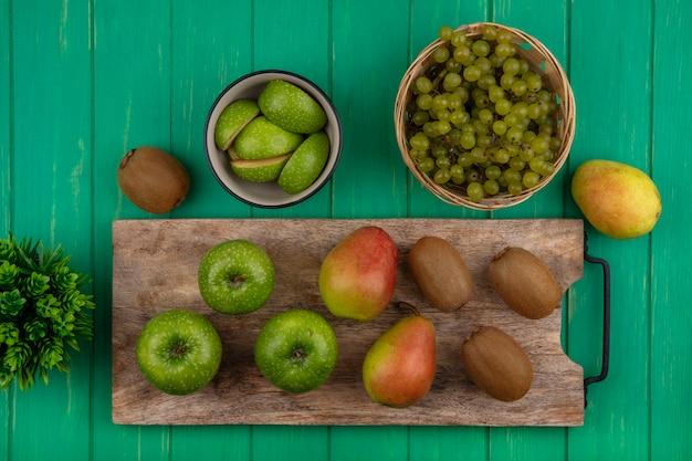 まな板にキウイと洋ナシ、緑の背景にバスケットに緑のブドウと上面図青リンゴ
