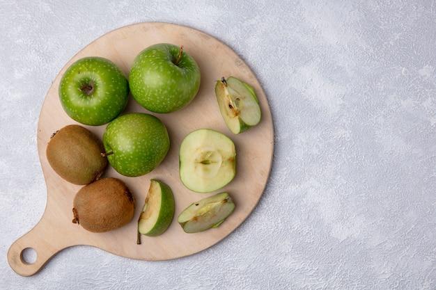 Vista dall'alto mele verdi con kiwi su un tagliere su uno sfondo bianco