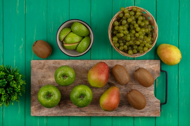 Top view green apples with kiwi and pear on a cutting board and green grapes in a basket on a green background