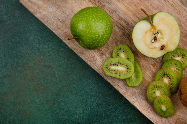 Top view green apples with kiwi slices on blackboard  on green background