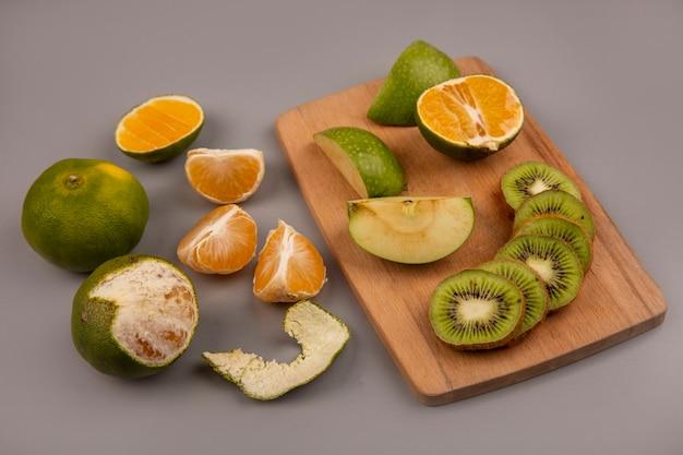 Vista dall'alto di mele verdi con fette di kiwi su una tavola di cucina in legno con mandarini isolati