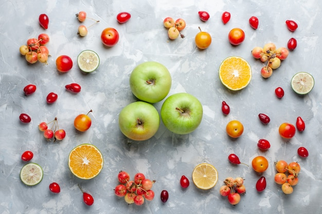 Vista dall'alto mele verdi con limone e ciliegie sulla scrivania bianca frutta bacca vitamina estate mellow