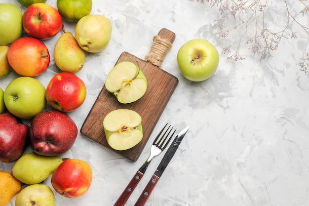 明るい白の背景に他の果物と青リンゴの上面図