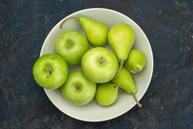 A top view green apples with pears inside white plate on the dark background fruit color pulp fresh