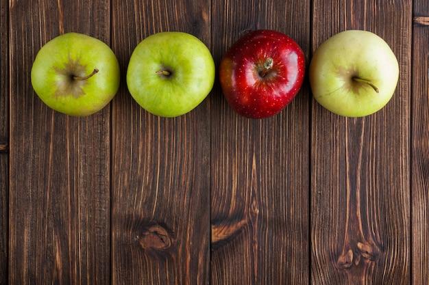 나무 배경에 빨간색 하나 상위 뷰 녹색 사과. 텍스트를위한 수평 여유 공간