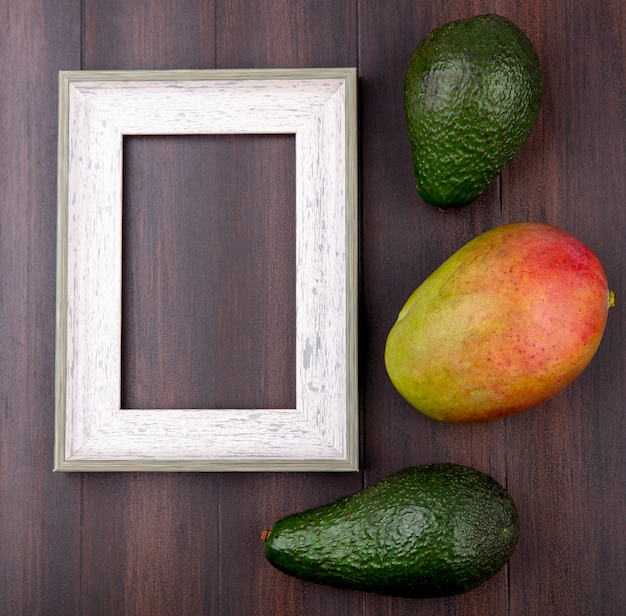Top view of green avocado with mango on a wooden surface