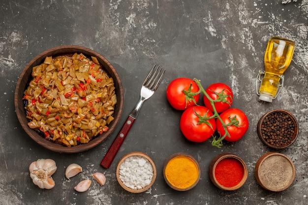 어두운 테이블에 페디셀 병이 있는 마늘 포크 토마토 옆에 있는 향신료 녹색 콩과 토마토의 상위 뷰 녹색 콩 그릇
