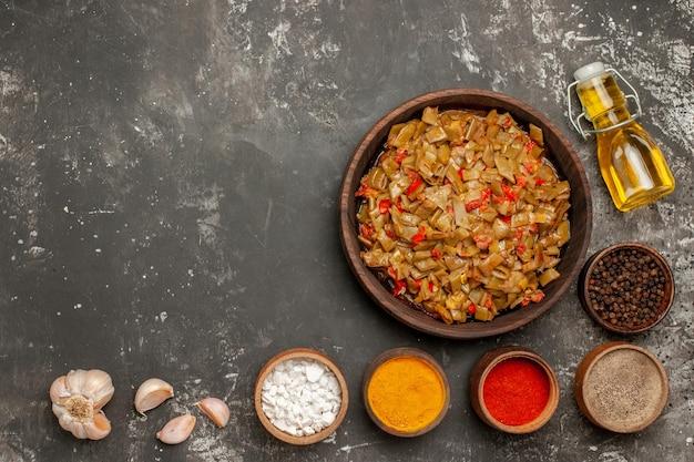 Vista dall'alto fagiolini ciotole di spezie aglio bottiglia di olio e piatto di fagiolini e pomodori sul tavolo