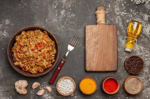 Vista dall'alto fagiolini fagiolini e pomodori accanto alla forchetta d'aglio bottiglia di olio il tagliere e ciotole di spezie sul tavolo scuro