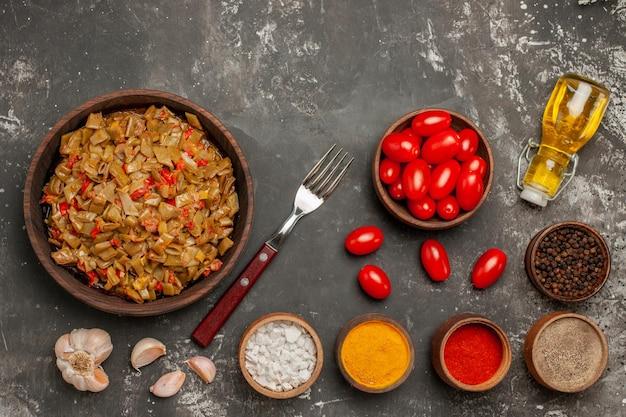 Vista dall'alto piatto di fagiolini di appetitosi fagiolini con pomodori accanto alla forchetta di aglio pomodori bottiglia di olio ciotola di spezie sul tavolo scuro