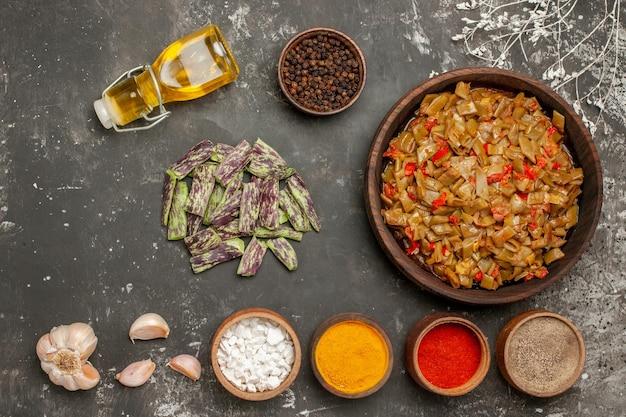 Vista dall'alto piatto di fagiolini di fagiolini accanto alla bottiglia di aglio di olio ciotola di spezie sul tavolo scuro