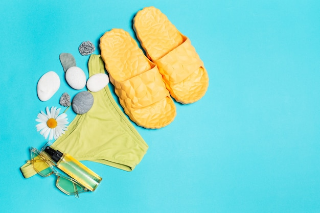Top view of green bikini, yellow slippers, sunglasses and oil tube decorated with chamomile flower