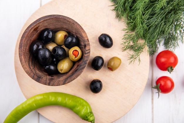 Top view of green and black olives in bowl and pepper on cutting board with dill and tomatoes on wooden surface