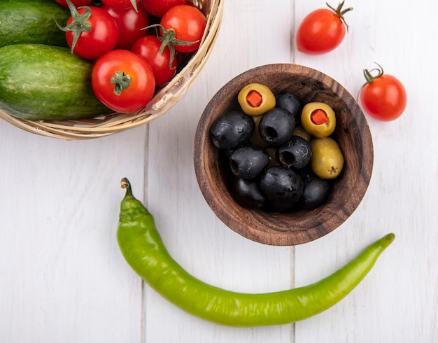 Top view of green and black olives in bowl and tomatoes cucumbers in basket and pepper on wooden surface