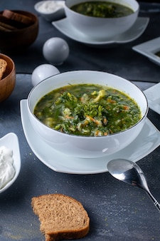 A top view green borsh vegetable soup along with sour cream and bread