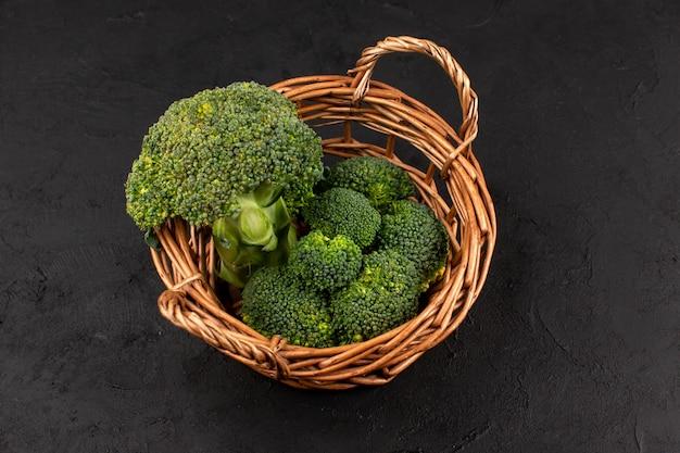Vista dall'alto broccoli verdi freschi maturi all'interno del cestino sul buio