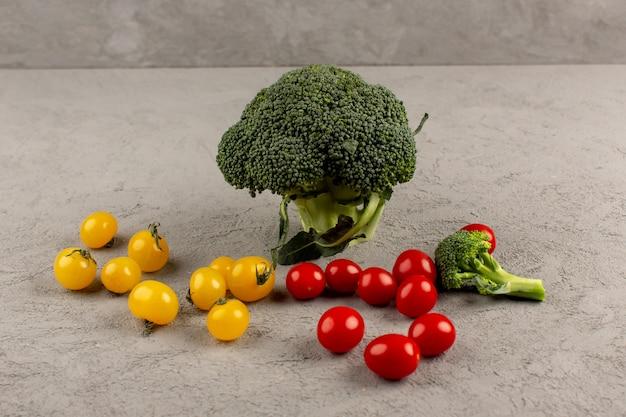 회색 바닥에 노란색과 빨간색 토마토와 상위 뷰 녹색 브로콜리