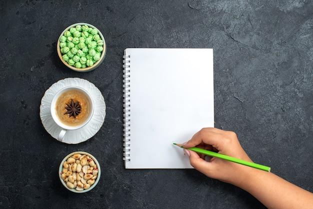灰色の背景にコーヒーとナッツのカップと緑のキャンディーの上面図ビスケットシュガーケーキ甘いクッキーキャンディー