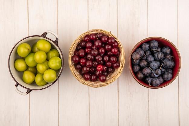 Vista dall'alto di prugna ciliegia verde su una ciotola con ciliegie rosse su un secchio con prugnole su una ciotola rossa su un fondo di legno bianco