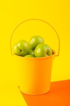Una ciliegia-prugna verde di vista superiore all'interno del canestro giallo sulla composizione acida della frutta arancio e gialla del fondo