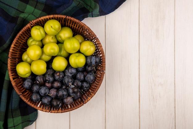 Vista dall'alto di prugna ciliegia verde con prugnole viola scuro su un secchio su una tovaglia controllata su un fondo di legno bianco con lo spazio della copia