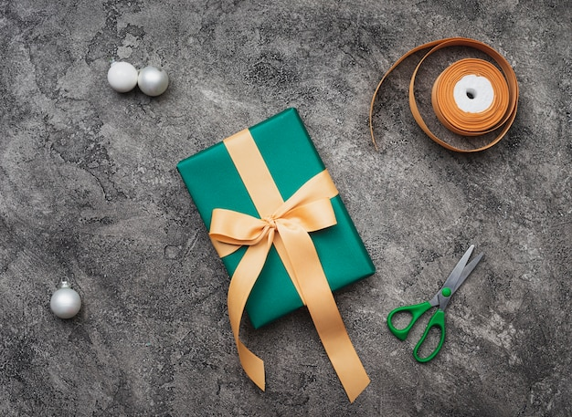 Top view of green christmas gift on marble background
