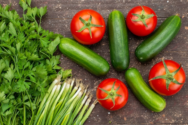 Вид сверху зеленые огурцы свежие и спелые с красными помидорами и зеленью на коричневых овощных растениях