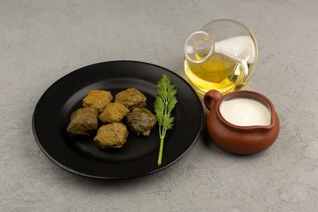 トップビューグレーのヨーグルトとオリーブオイルと一緒に黒い皿の中のミンチ肉と緑のドルマ