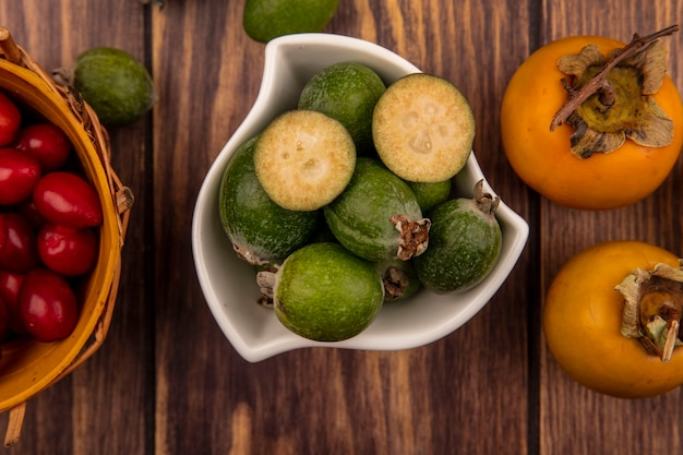Top view of green feijoas on a bowl with cornelian cherries on a bucket with persimmon fruits isolated on a wooden wall