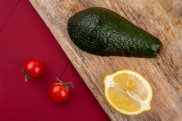 Top view of green and fresh avocado on a wooden kitchen board with lemon slice and cherry tomatoes on red surface
