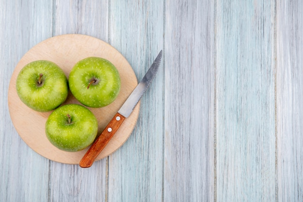 Top view of green fresh delicious apples on a cutting kitchen board with knife on grey wooden surface