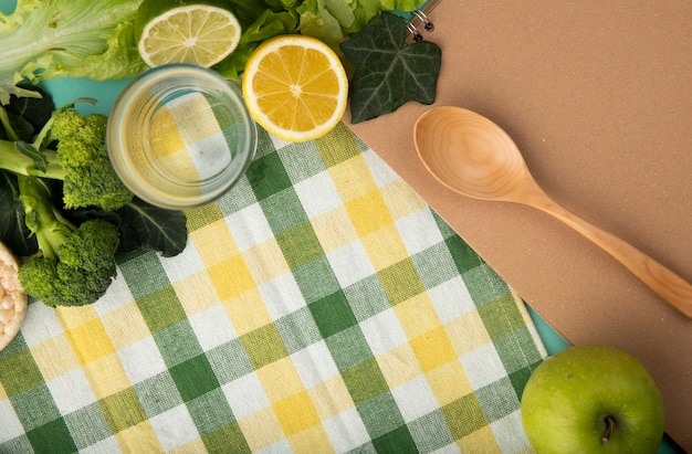 Top view green fruits and vegetables brocoli lettuce ivy leaves glass of water wooden spoon apple slice of lemon and lime with copy space on tablecloth