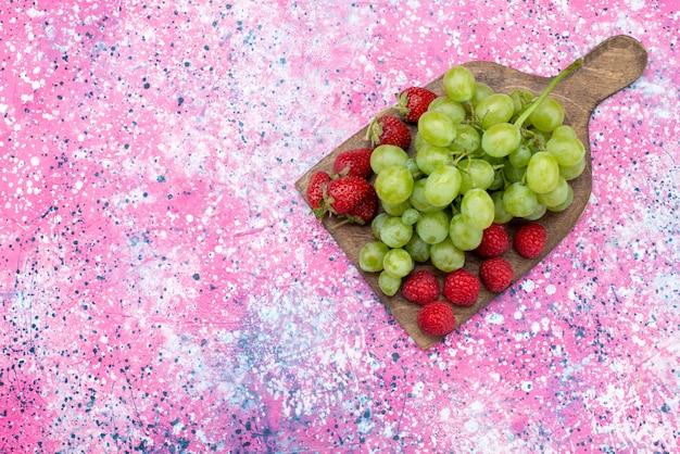 色付きの背景の果物イチゴビタミンカラー写真に赤いイチゴと一緒に平面図の緑のブドウ