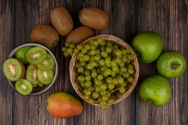 Top view green grapes in a basket with green apples and kiwi with slices in a bowl on a wooden background