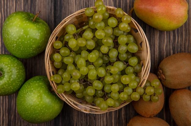 Vista dall'alto uva verde in un cesto con mele verdi e kiwi su uno sfondo di legno