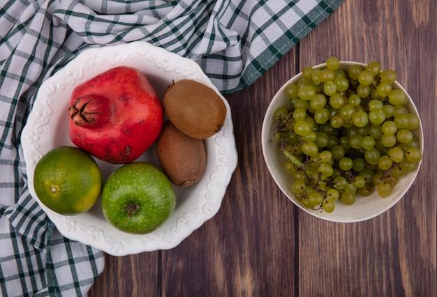 木製の壁に緑の市松模様のタオルの上にザクロのリンゴキウイとみかんとボウルの上面図緑のブドウ
