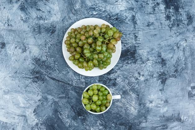 지저분한 석고 배경에 흰색 접시와 컵에 상위 뷰 녹색 포도. 수평