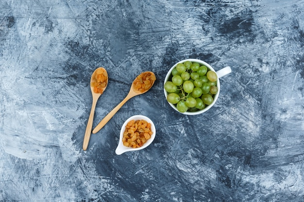 Top view green grapes in white cup with raisins on grungy plaster background. horizontal