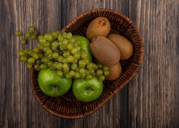 Top view green grapes with apples and kiwi in a basket on a wooden background