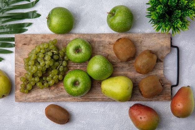 Vista dall'alto uva verde con mele verdi e kiwi su un supporto con pere su uno sfondo bianco