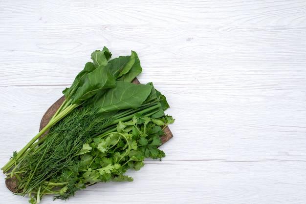 Вид сверху зеленая зелень на коричневом деревянном столе и светлом фоне зеленый овощной лист